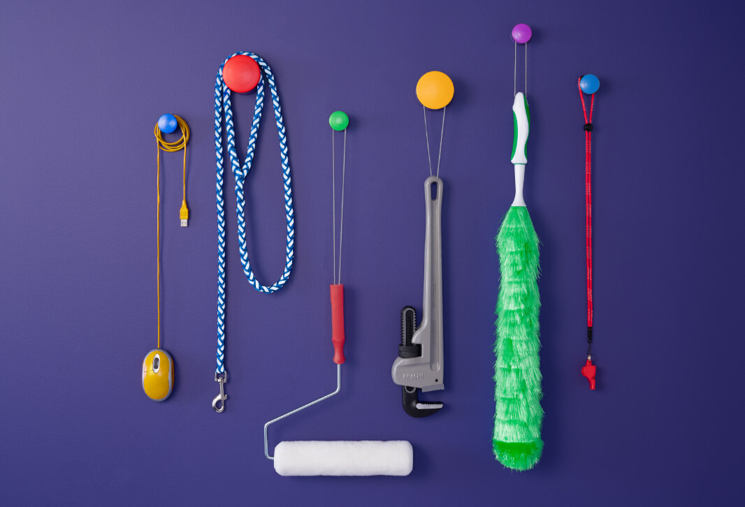Computer mouse, dog leash, paint roller and various tools suspended from utility hooks