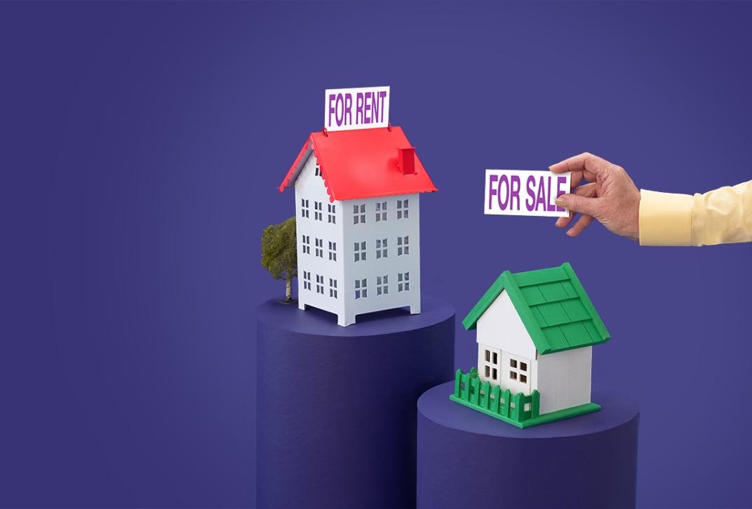 Maison rouge miniature avec pancarte « À vendre », maison verte avec pancarte « À vendre » mise en place