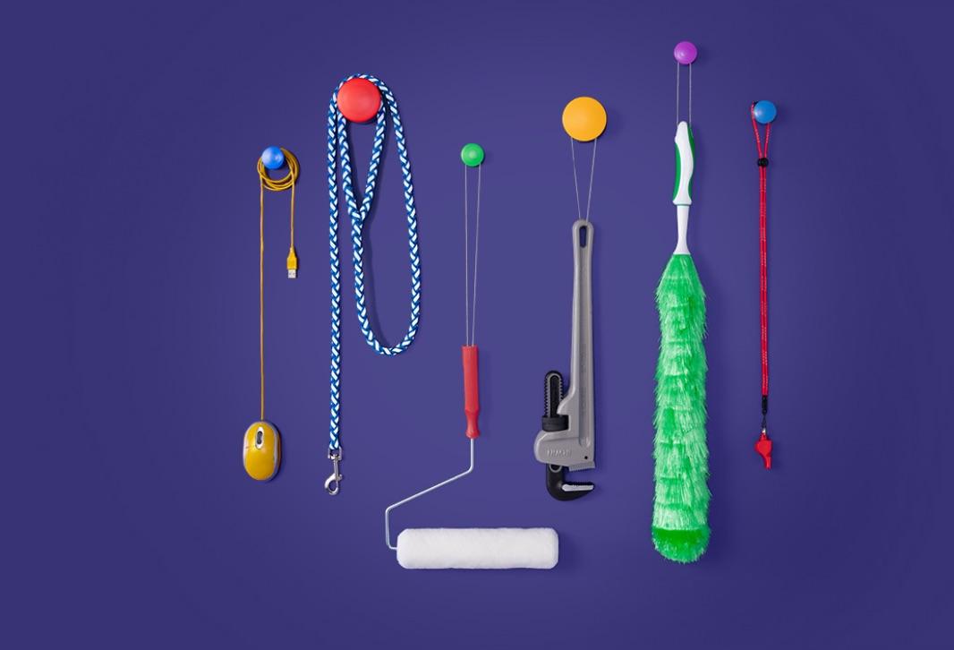 Souris d'ordinateur, laisse de chien, rouleau de peinture et divers outils suspendus sur des crochets
