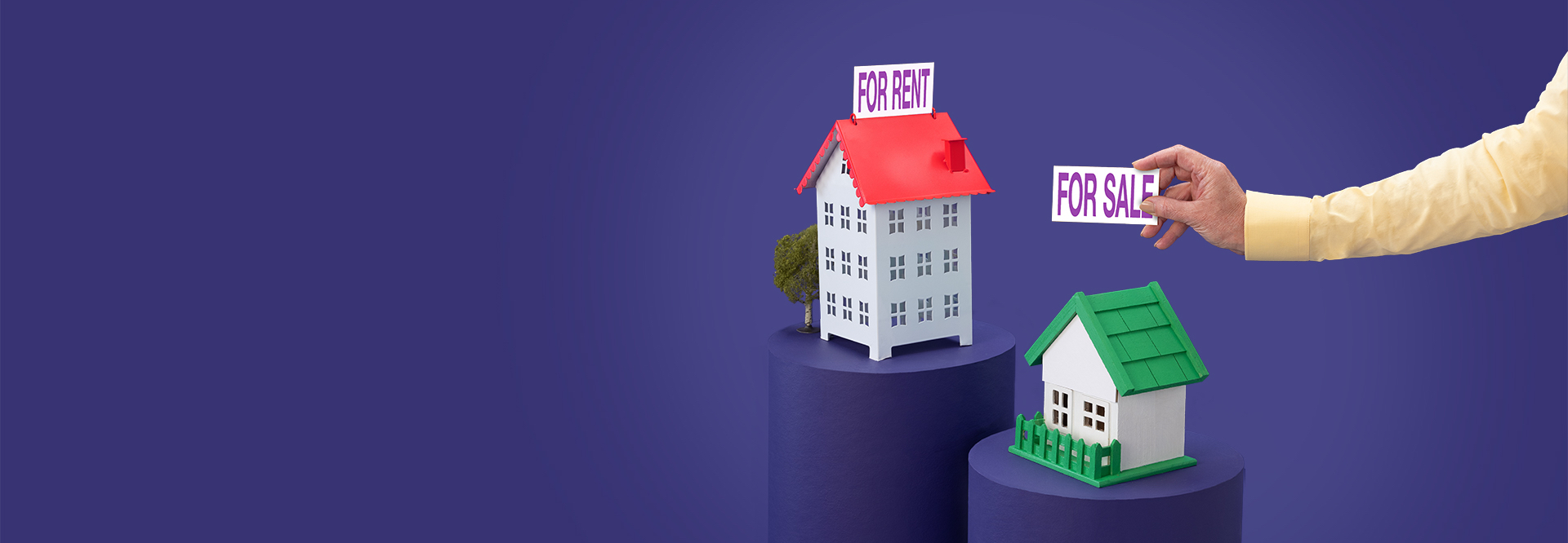 Red miniature house with a For Rent sign, green house with For Sale sign being added
