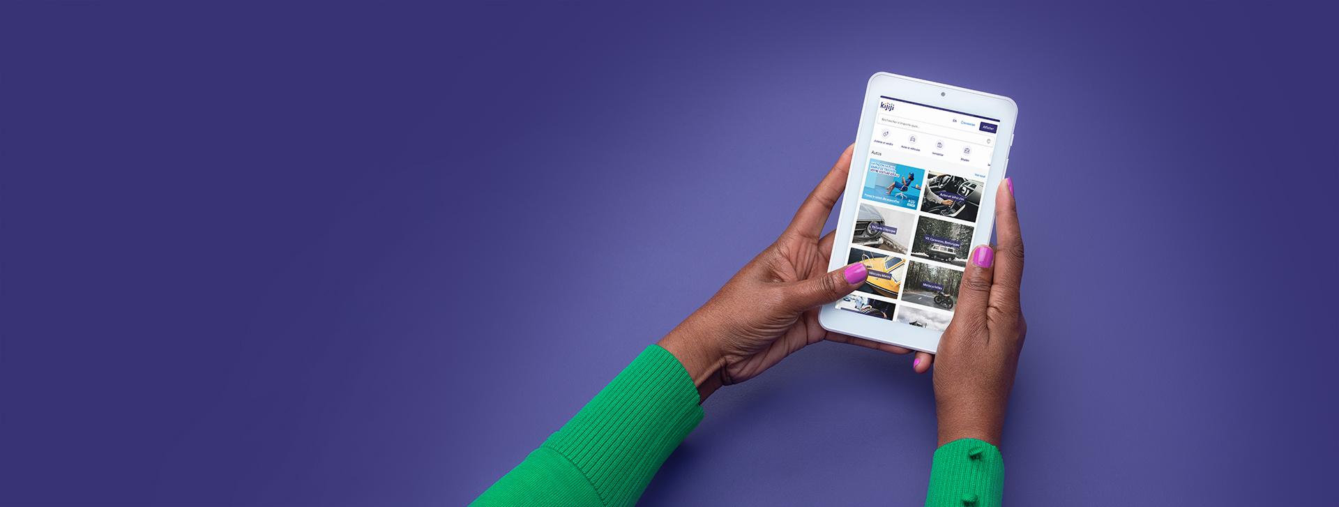 Deux mains tenant un appareil mobile sur lequel on voit le site Kijiji