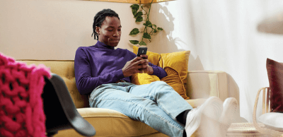 A man sits on his couch in his living room while looking at his phone